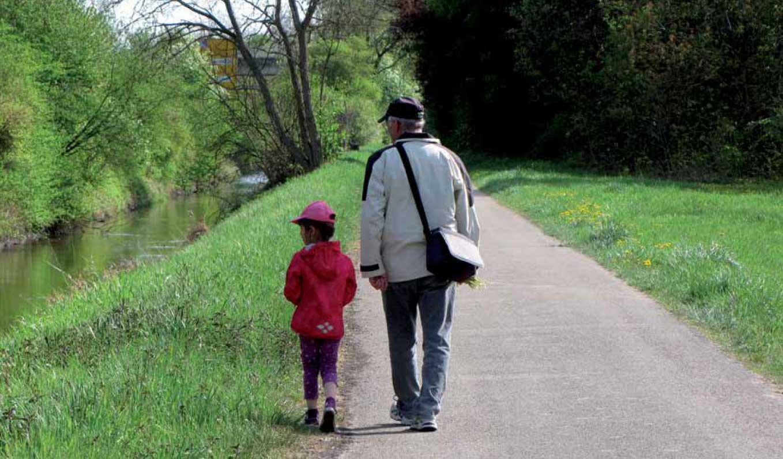Mann mit Kind auf Spaziergang an einem Bach entlang
